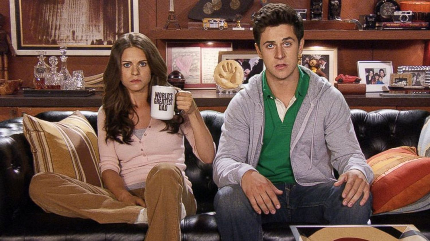 Image of man and woman on the couch staring straight in disbelief, with the woman holding a cup that says World's Greatest Dad
